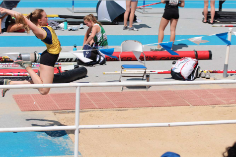 Soaring Sydney: Taking off on a long jump, senior Sydney Willits flies through the air, landing into the sand pit. With Willits' family by her side, she plans to take her final track and field season at South in stride.