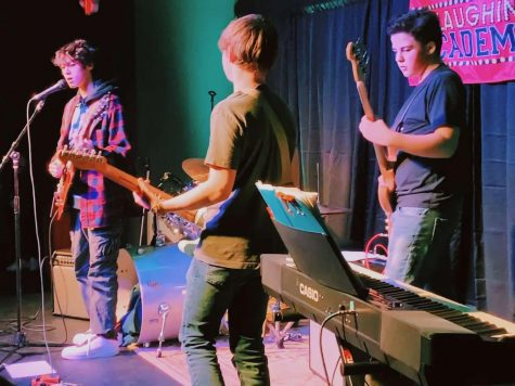 Guitar greatness: Rocking out at the Laughing Academy, a local improv school, sophomores Henry Najem, Terry Treger and Johnny Rolfes (left to right) play during the summer of 2020. More recently, their band, Candy for Breakfast, won Battle of the Bands, a competition at South between various bands where students vote for a winner. Photo courtesy of Johnny Rolfes.